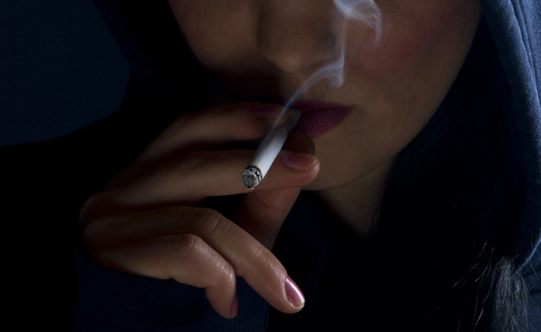 Woman hood smoking in dark
